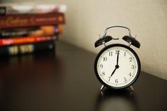 Vintage alarm clock on dark brown surface. Shows 7 o'clock. Pile Royalty Free Stock Image