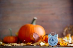 Vintage alarm clock and maple tree leaves with pumpkins. On yellow wooden background with bokeh. Autumn season image style for Thaksgiving holiday Stock Images