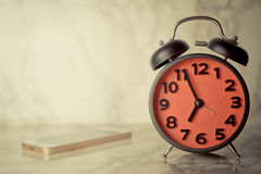 Vintage alarm clock with mobile phone Stock Images