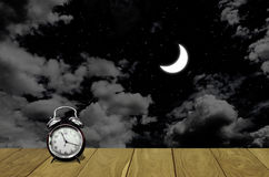 Vintage alarm clock with moon in night sky. Background Royalty Free Stock Photography