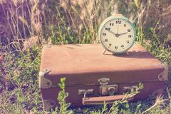 Vintage alarm clock on an old classic brown leather suitcase on. A background of green grass. Retro toning. Travel concept royalty free stock photos