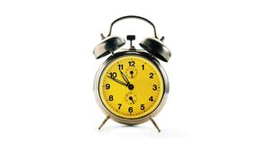 Vintage alarm clock over a white background. Time running backwards. stock footage
