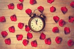 Vintage alarm clock and petals Stock Photography