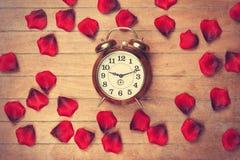 Vintage alarm clock and petals Stock Photos