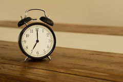 Vintage alarm clock on rustic wood table. Shows 7 o'clock. Royalty Free Stock Photography