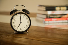Vintage alarm clock on rustic wood table. Shows 7 o'clock. Pile Stock Photos
