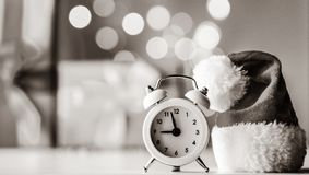 Vintage Alarm clock in Santa Claus hat with Christmas gift. And Ligths on background stock photography