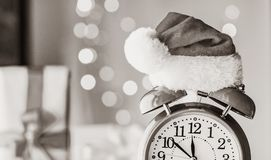 Vintage Alarm clock in Santa Claus hat with Christmas gift. And Ligths on background royalty free stock image