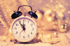 Vintage alarm clock showing five to midnight on abstract glitter Royalty Free Stock Photo