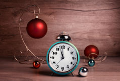 Vintage alarm clock showing five to twelve with Christmas bauble Stock Photo