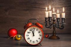 Vintage alarm clock showing five to twelve and Christmas baubles Stock Image