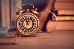 Vintage alarm clock showing five to twelve among old books in st Stock Photos