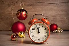 Vintage alarm clock showing five to twelve on wood Royalty Free Stock Photos