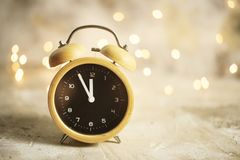 Vintage alarm clock showing midnight. christmas and bokeh, royalty free stock images