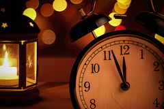 Vintage alarm clock is showing midnight. It is twelve o`clock, christmas and bokeh, holiday happy new year festive concept. On light lantern background royalty free stock photo