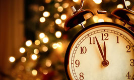 Vintage alarm clock is showing midnight. It is twelve o`clock, christmas and bokeh, holiday happy new year festive concept. On light tree background Royalty Free Stock Images