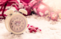 Vintage alarm clock on snow on christmas presents background Royalty Free Stock Photography