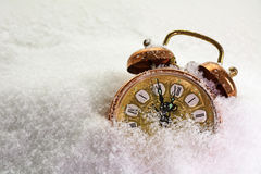 Vintage alarm clock in the snow shows five minutes before twelve Stock Image