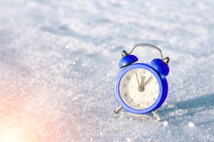 Vintage alarm clock on the snow at sunset. The concept of Christmas and New Year. Stock Photography