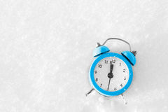 Vintage alarm clock on the snow at sunset. The concept of Christmas and New Year. Stock Images