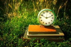 Vintage alarm clock on a stack of old books against a background. Of green grass. Copy space. Time concept, business planning Stock Photo