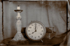 Vintage alarm clock. Vintage still life of alarm clock, candle and books in grooved style Stock Photography