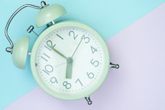 Vintage alarm clock on sweet pastel colored paper top view, back. Flat lay vintage alarm clock on sweet pastel colored paper top view, background texture, pink royalty free stock image