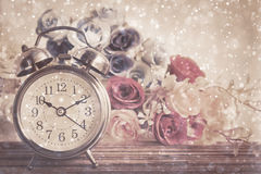 Vintage alarm clock on table. 10.10 am with bokeh and rose flower on wood table Royalty Free Stock Photos