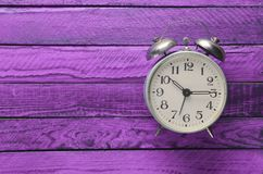 Vintage alarm clock on a violet wooden background. Top view.  Royalty Free Stock Photos