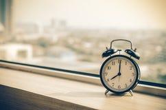 Vintage alarm clock at windows at early morning Royalty Free Stock Photography