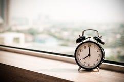 Vintage alarm clock at windows at early morning Royalty Free Stock Photo