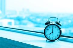 Vintage alarm clock at windows at early morning Royalty Free Stock Photos