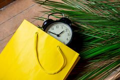 Vintage alarm clock in yellow bag and palm leaves. On wooden table. Above view royalty free stock image