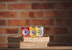 Vintage alarm clocks and old books royalty free stock images