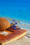 Vintage album on the sand with coconut shell Stock Image