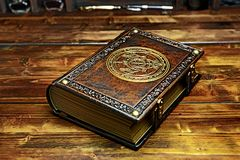 Vintage Alchemist book with gilded paper edges and the symbol lay down to the wooden table. In the dark atmosphere royalty free stock photo