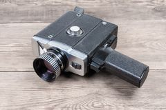 Vintage amateur electric movie camera on an old wooden surface. Vintage amateur film movie camera powered by electric motor on an old wooden surface royalty free stock photography