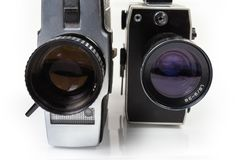 Vintage amateur mechanical and electric movie cameras close-up. Two old vintage amateur film movie cameras powered by clockwork motor and electric motor. View stock photography