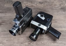 Vintage amateur mechanical and electric movie cameras on wooden surface. Two old vintage amateur film movie cameras powered by clockwork motor and electric motor royalty free stock image