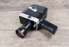 Vintage amateur mechanical movie camera on an old wooden surface. Vintage amateur film movie camera powered by clockwork motor on an old wooden surface stock images