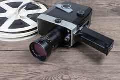 Vintage amateur movie camera against of films on wooden surface. Vintage amateur film movie camera powered by clockwork motor against of reels of motion picture royalty free stock image