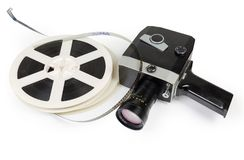 Vintage amateur movie camera and reels of Super 8mm films. Old vintage amateur film movie camera powered by clockwork motor and reels of color motion picture stock photography