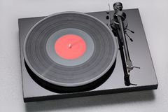Turntable playing vinyl close up with needle on the record with grey background Royalty Free Stock Photography