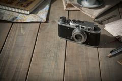 Vintage analogue film camera on a wooden table, map, notepad, pencil. royalty free stock photography