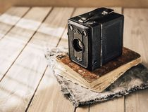 Vintage analogue film camera on a wooden table, old book, clothl. Retro photo. Copy space. royalty free stock images