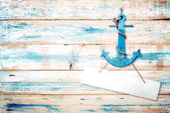 Vintage anchor on old wooden background with blue paint. Vintage wood texture from beach in summer Royalty Free Stock Images