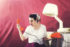 Vintage angry housewife chats on the phone in Hair salon Stock Images