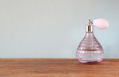 Vintage antigue perfume bottle, on wooden table.  Royalty Free Stock Photo