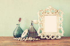 Vintage antigue perfume bottles with old picture frame, on wooden table. retro filtered image.  Royalty Free Stock Photo
