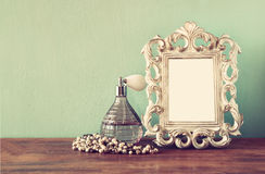 Vintage antigue perfume bottles with old picture frame, on wooden table. retro filtered image.  Stock Photos